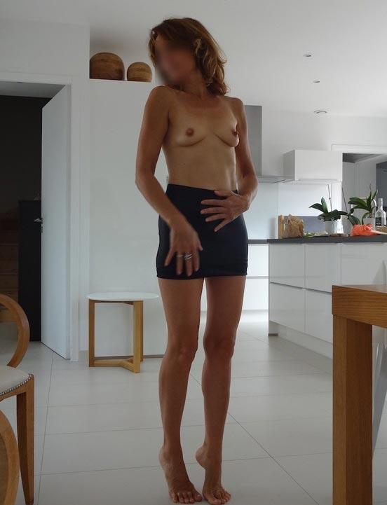 Femme Cougar de Paris en mini-jupe et seins nus, chez elle dans le 12ème arrondissement